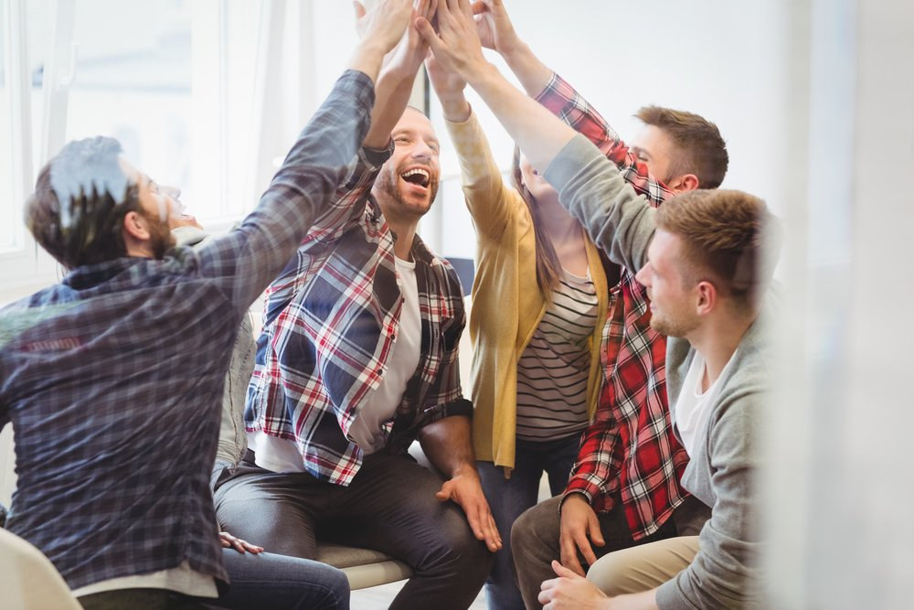 Successful creative business people giving high-five in meeting room at creative office